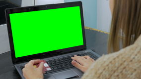Woman looking at laptop with green screen. Young woman buying goods from the internet and entering number security code from credit card on laptop with green stock video footage