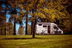 Family vacation travel, holiday trip in motorhome. Woman looking at the laptop near the camping . Caravan car Vacation. Family vacation travel, holiday trip in stock photos