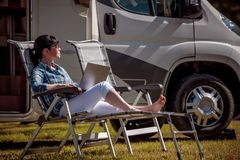Family vacation travel, holiday trip in motorhome RV. Woman looking at the laptop near the camping . Caravan car Vacation. Family vacation travel, holiday trip stock images