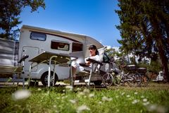 Family vacation travel, holiday trip in motorhome RV. Woman looking at the laptop near the camping . Caravan car Vacation. Family vacation travel, holiday trip Stock Image