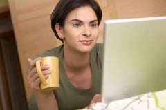 Woman looking at laptop screen smiling at home Royalty Free Stock Images
