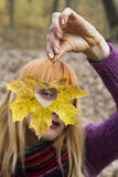 Woman looking through  leaf with heart shaped hole. Woman looking through autumn leaf with heart shaped hole Royalty Free Stock Photos