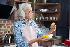 Woman looking at lemons in kitchen Stock Photos