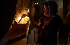 A woman is looking at a lighted bunch of 33 candles. By Jerusalem pilgrim`s Christian tradition a bunch of 33 candles shall be singed by the fire of the candles Stock Photography