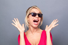 Woman looking like star using both hands and facial expression for surprise. Surprise concept - bubbly young blond woman looking like a star with her sunglasses Royalty Free Stock Photos