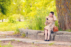Woman looking at a little mirror. Elegant businesswoman sitting on a stone wall during a sunny spring day, and setting her hair looking herself in a little stock photo