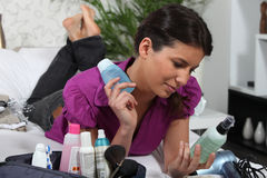 Woman looking at lotion bottles Royalty Free Stock Photography