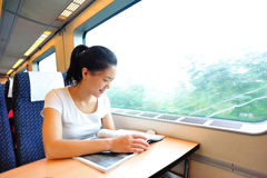 Woman looking magazine interior of train. Young asian woman looking magazine interior of train/subway Royalty Free Stock Photos
