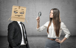 Woman is looking through a magnifier at a businessman with a box on his head with a pokerface. Recruitement. Personnel hiring. Candidates for job Royalty Free Stock Photo