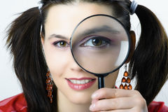 Woman looking through magnifying. Pretty young woman looking through magnifying Royalty Free Stock Images