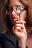Woman looking through magnifying glass Royalty Free Stock Photo