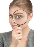 Woman looking through a magnifying glass Royalty Free Stock Photo
