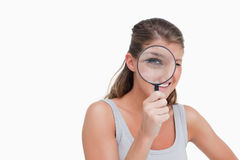 Woman looking through a magnifying glass Stock Photography