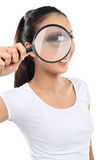 Woman looking through a magnifying glass Royalty Free Stock Photos