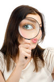 Woman looking through a magnifying glass Stock Image