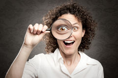Woman looking through magnifying glass Royalty Free Stock Photos