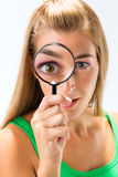 Woman looking through magnifying glass. Or loupe royalty free stock image