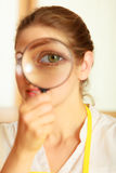 Woman looking through magnifying glass. Stock Photos