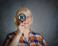 Woman looking through a magnifying glass. Stock Photography