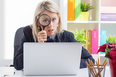 Woman looking through a magnifying glass Stock Photos