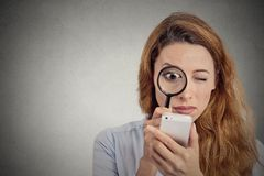 Woman looking through magnifying glass on smart phone screen Royalty Free Stock Image