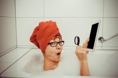 Woman looking with magnifying glass in tablet computer Royalty Free Stock Photography