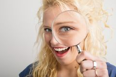 Woman looking through magnifying glass. Young and beautiful woman looking through magnifying glass Royalty Free Stock Images