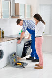 Woman Looking At Male Worker Repairing Oven. Young Woman Looking At Male Worker In Overall Repairing Oven In Kitchen Stock Photo