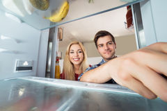 Woman Looking At Male Worker Repairing Refrigerator. Young Happy Woman Looking At Male Worker Repairing Inside The Refrigerator Royalty Free Stock Images