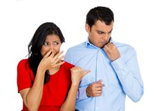 Woman looking at man closing, covering nose Stock Image