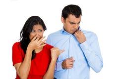 Woman looking at man closing, covering nose stock image