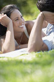 Woman Looking At Man While Lying In Park. Happy young women looking at men while lying on blanket in park Stock Image