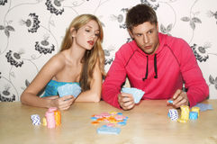 Woman Looking At Man's Playing Cards stock photo