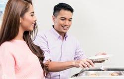 Woman looking at man serving buffet food stock photo