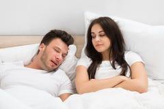 Woman looking at man snoring in bed at home. Angry Young Woman Looking At Man Snoring In Bed At Home Royalty Free Stock Photos