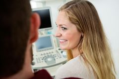 Woman Looking At Man With Ultrasound Machine In stock image
