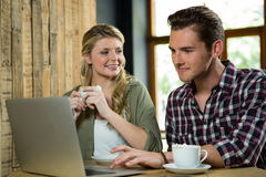 Woman looking at man using laptop in coffee shop Royalty Free Stock Photo