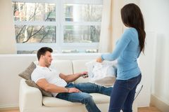 Woman looking at man using remote control Royalty Free Stock Images