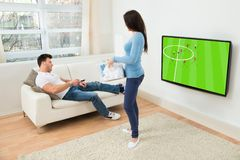 Woman looking at man watching football match on television Royalty Free Stock Photo