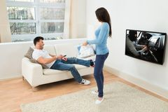 Woman looking at man watching movie on television Stock Photo