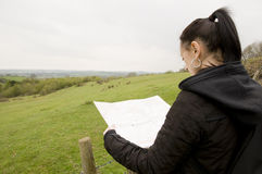 Woman looking at map with countryside view Stock Images