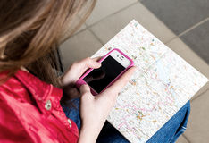 Woman looking at the map and telephone number. She is studying the route. Close-up Royalty Free Stock Image