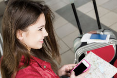 Woman looking at the map and telephone number. She is studying the route. Close-up.  Stock Photography