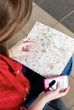 Woman looking at the map and telephone number. She is studying the route. Close-up Stock Photography