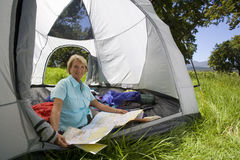 Woman looking at map in tent Stock Photo