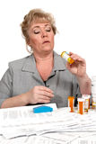 Woman looking into medicine bottle Stock Photos