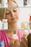 Woman Looking in Medicine Cabinet. A young woman is reading the labels of two medicine containers from her medicine cabinet. Vertical shot stock photo