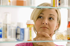 Woman Looking in Medicine Cabinet Royalty Free Stock Images