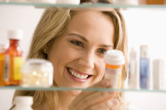 Woman Looking in Medicine Cabinet. A young woman is looking through her medicine cabinet and smiling. Horizontal shot stock images