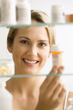 Woman Looking in Medicine Cabinet. A young woman looks through a medicine cabinet and smiles at the camera. Vertical shot stock photography